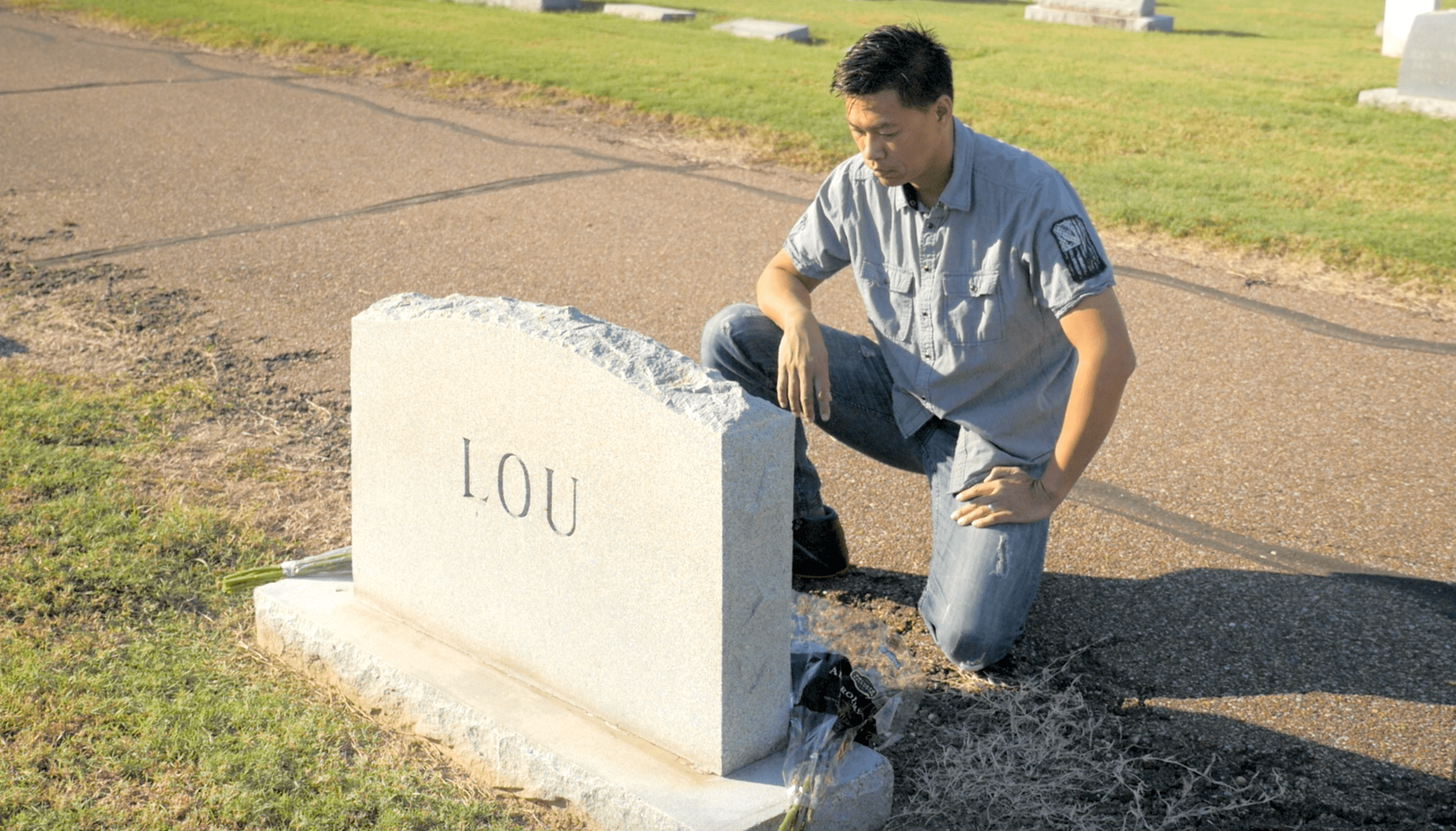"Far East Deep South Film Still of person kneeling at a tombstone engraved ""Lou"""