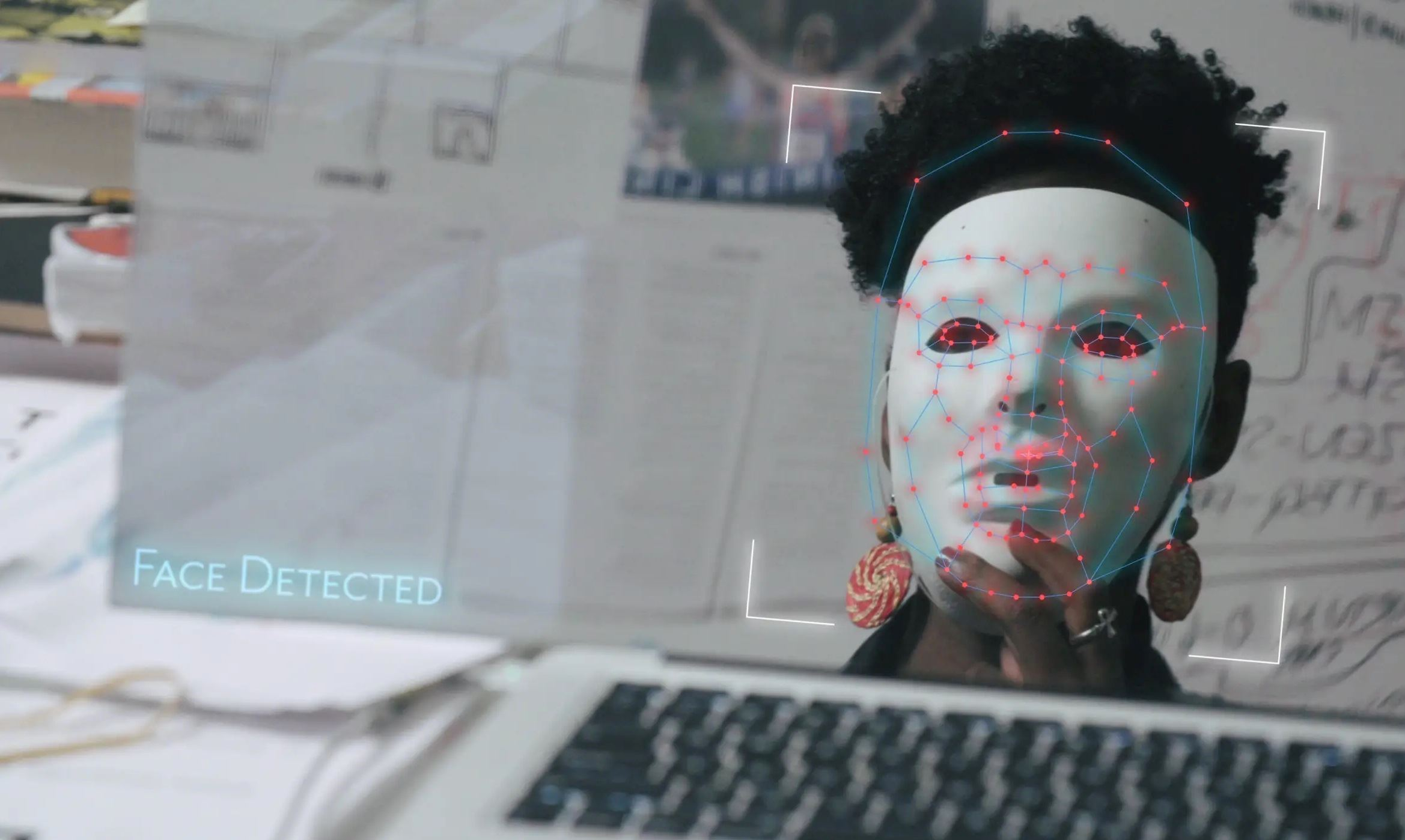 Coded Bias Film Still woman of color holds white mask up to her face